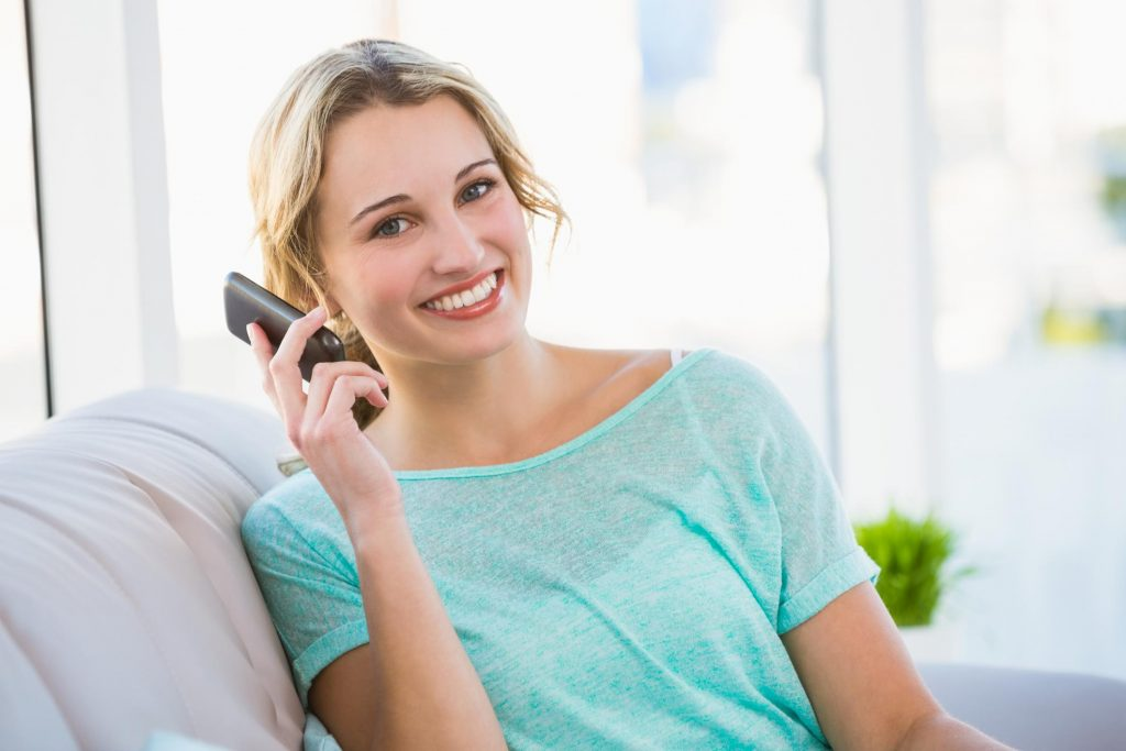 girls smiling talking to her phone
